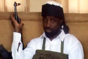 Abubakar Shekau, the leader of Nigeria's Boko Haram Islamist militants, dressed in a black turban and a white gown and bullet-proof vest, holding an AK 47 rifle.